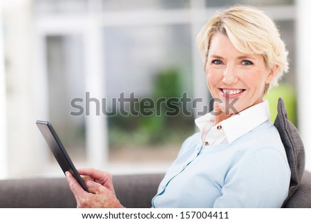 elegant middle aged woman using tablet pc at home - stock photo