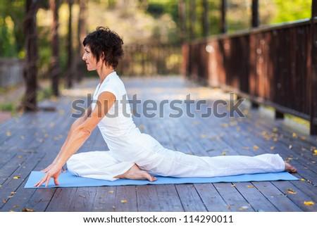 elegant middle aged woman yoga stretching - stock photo