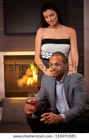 Elegant mixed race couple at home by fireplace, man holding glass of wine and cigar. - stock photo