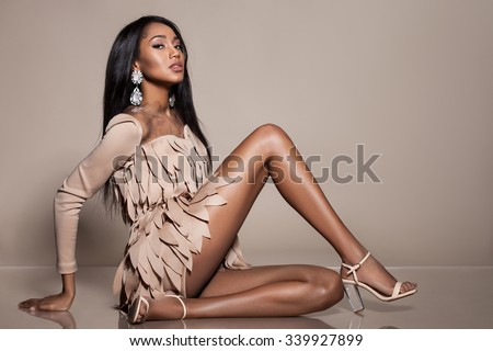 Elegant mulatto girl on beige background - stock photo