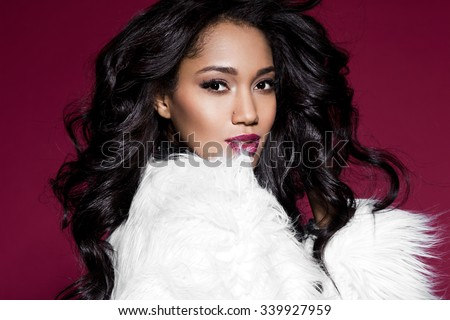 Elegant mulatto girl with fur - stock photo