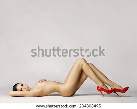 elegant naked woman in red shoes laying on white background - stock photo