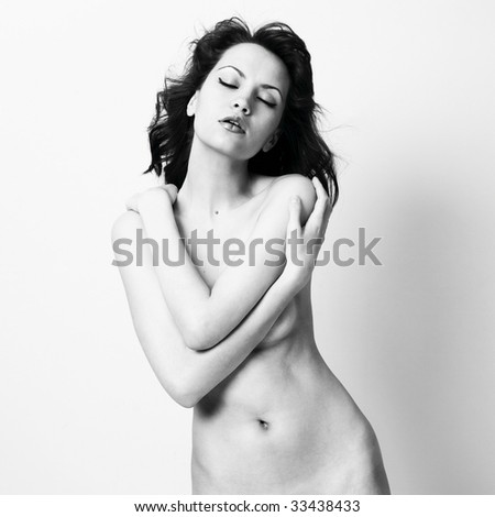 Elegant nude woman with curly hair. Studio portrait. - stock photo