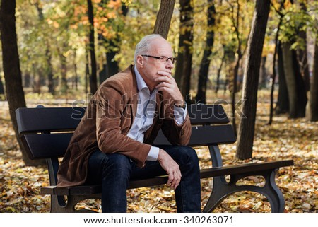 elegant old man with white hair sitting and thinking on a bench outside - stock photo