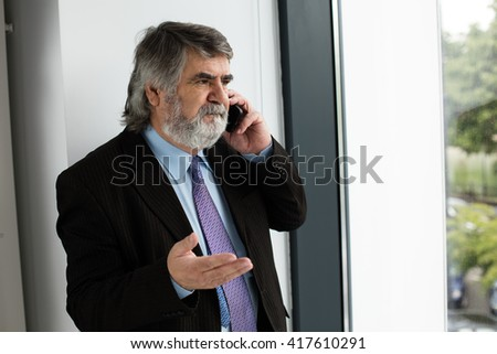 elegant old men having a conversation at cellphone next to a window