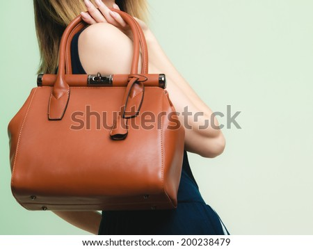 Elegant outfit. Closeup of brown leather bag handbag in hand of stylish woman fashionable girl on green. Female fashion. - stock photo