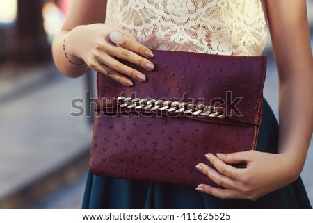Elegant outfit. Closeup of leather bag in hands of stylish woman. Fashionable girl on the street. Female fashion. City lifestyle. Toned - stock photo