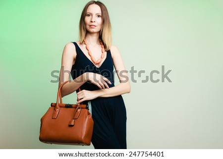 Elegant outfit. Stylish woman fashionable girl with brown leather handbag bag on green. Fashion and female beauty. - stock photo