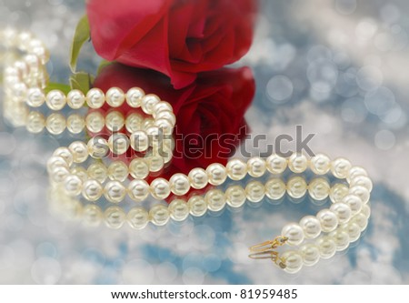 Elegant pearls over glass with clouds and rose very shallow depth of field - stock photo