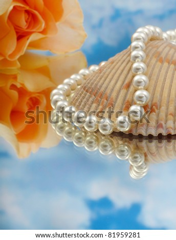 Elegant pearls over glass with clouds, shell, and rose very shallow depth of field - stock photo