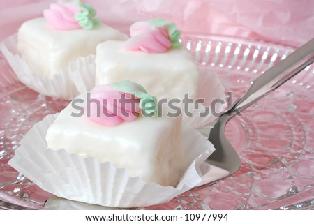 Elegant petit fours on a crystal plate with cake server.  Background of pastel pink tissue paper.  Close-up with shallow dof. - stock photo
