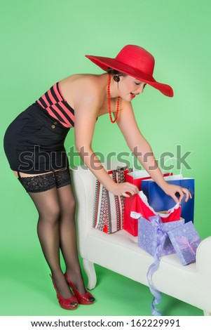 Elegant pin up girl unwrapping a sexy present - stock photo