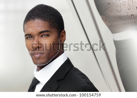 Elegant portrait of a great looking successful young businessman against modern reflective metal background - stock photo