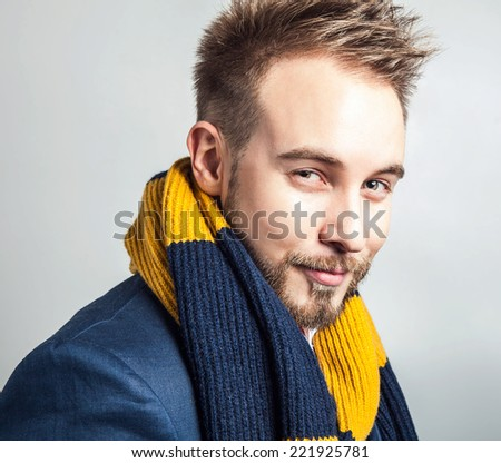 Elegant & Positive young handsome man in colorful scarf. Studio fashion portrait.