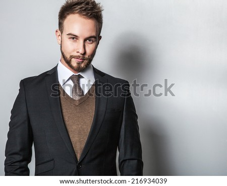 Elegant & Positive young handsome man in costume. Studio fashion portrait.
