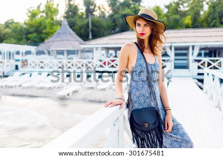 Elegant pretty slim woman with straw hat and long beach dress posing near luxury resort near the beach .  Wearing stylish  boho bag . - stock photo