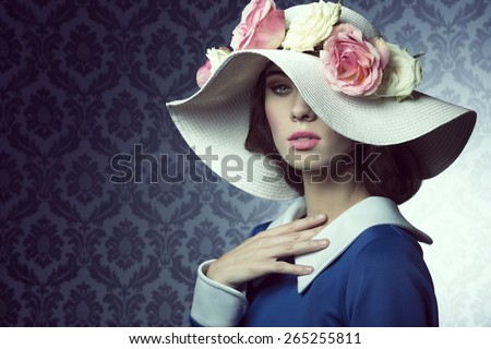 elegant pretty woman in blue dress with a spring white hat , with pink and white roses over . - stock photo