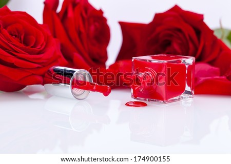 Elegant red nail varnish in a stylish bottle surrounded by romantic red roses with the brush lying alongside the open bottle with a droplet on the white surface below - stock photo
