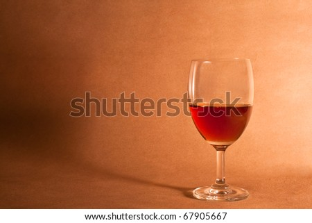 elegant red wine glass on brown wooden background