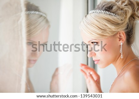 Elegant Reflection of a Beautiful blond bride in mirror in modern glass building penthouse - stock photo