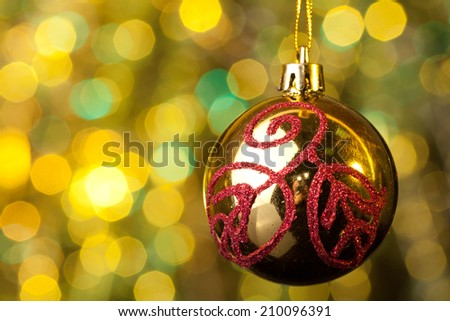Elegant reflective Christmas ornament hanging in front of yellow and green Christmas lights. - stock photo