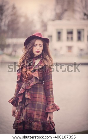 Elegant retro beautiful young woman in a vintage hat burgundy color and the old  English coat walks on cold autumn park, fashion, style