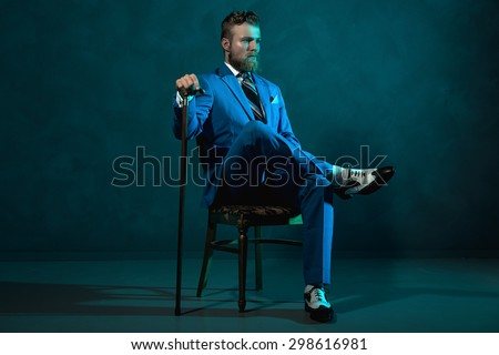 Elegant retro style gentleman with a cane sitting in a chair looking thoughtfully off to the side in a blue toned dark environment with copyspace - stock photo