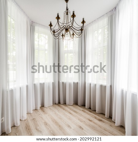 Elegant room interior with wooden floor, white curtain and chandelier - stock photo