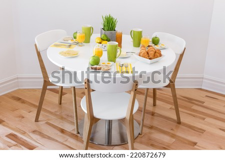 Elegant round table with tasty breakfast for three. - stock photo
