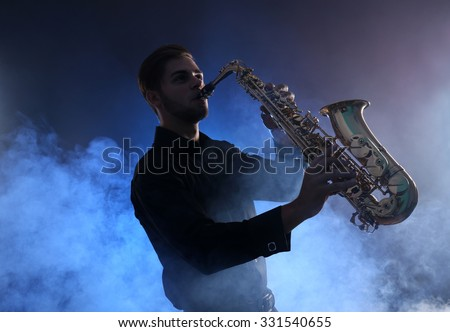 Elegant saxophonist plays jazz  in blue smoke