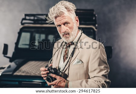 Elegant Senior Bearded Man with Blond Hair Holding his Camera and Looking Into Distance Against his Four-Wheel Vehicle on a Fuzzy Night. - stock photo