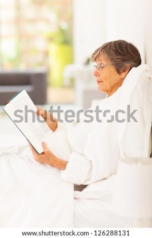 elegant senior woman lying on bed reading a book - stock photo