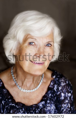 Elegant senior woman portrait on dark background - stock photo