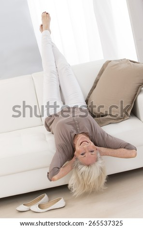 Elegant Senior woman relaxing on a sofa with head upside down - stock photo