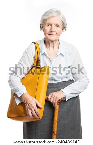 Elegant senior woman with walking stick standing over white - stock photo
