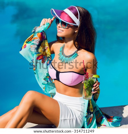 Elegant sensual woman   in bright dammer vacation clothes sitting near big pool and drink exotic  cocktail . Bright summer colors. Stylish accessories and sunglasses. Beach party. - stock photo