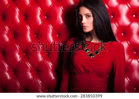 elegant sensual young brunette woman in red dress standing near wall