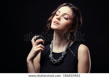 Elegant sensual young woman holding perfume, Fashion photo