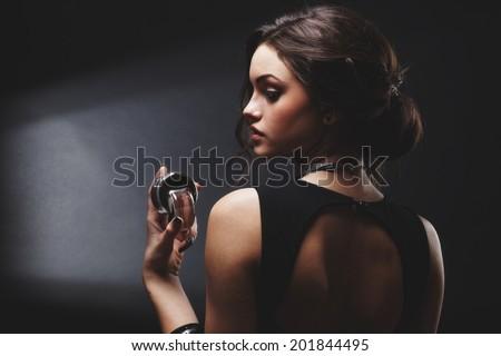 Elegant sensual young woman holding perfume, Fashion photo - stock photo