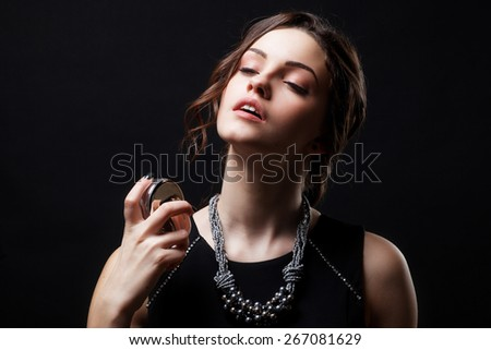 Elegant sensual young woman holding perfume. Fashion photo of young magnificent woman. Girl posing. Studio photo. Perfect Skin. Professional Make-up.Makeup. Fashion Art.Vogue Style.  - stock photo