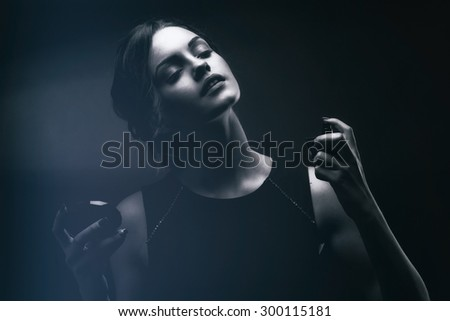 Elegant sensual young woman holding perfume. Fashion photo of young magnificent woman. Girl posing. Studio photo. Perfect Skin. Professional Make-up. Makeup. Fashion Art. Vogue Style.  - stock photo