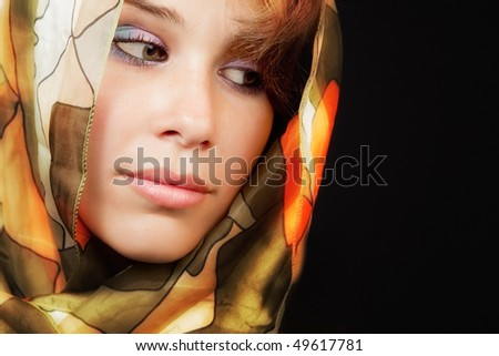 Elegant sensual young woman with colorful vail over black - stock photo