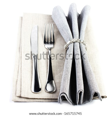 Elegant  Serving table setting place in silver and grey color isolated on white background. Linen textile napkin with cutlery - knife and fork, - stock photo