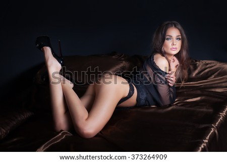Elegant sexy brunette woman lying in bed, looking at camera. Perfect slim body. - stock photo