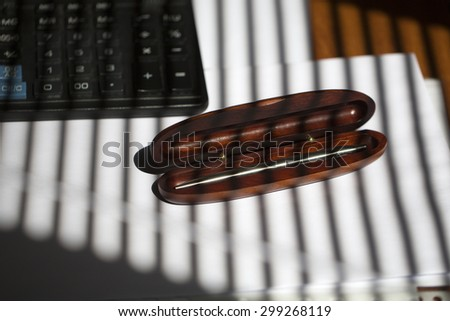 Elegant silver ball-point pen in brown wooden open case near black keyboard lying on white envelope and sheet of empty paper on office table on jalousie shadow background, horizontal picture - stock photo