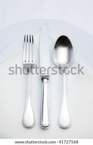 elegant silverware setting on plate with white cloth - stock photo
