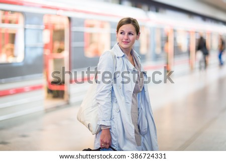 Elegant, smart, young woman taking the metro/subway - stock photo