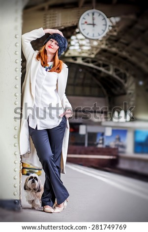 Elegant smiling ginger hair womans and hih tzu dog on the platform under the clock waiting train at the Vitebsk railway station