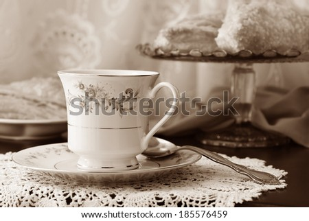 Elegant still life of beautiful vintage teacup and saucer with sweet pastries on pedestal plate in background. Closeup in sepia tones with shallow dof.  - stock photo