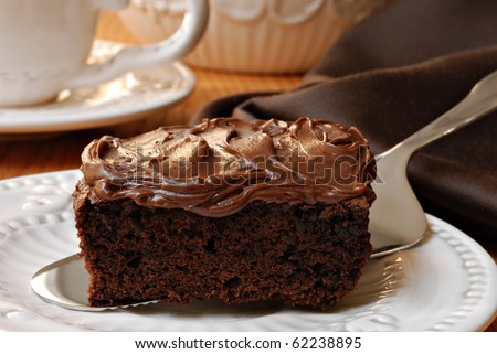 Elegant still life of chocolate frosted brownie being served with teacup and napkin in background.  Macro with shallow dof. - stock photo